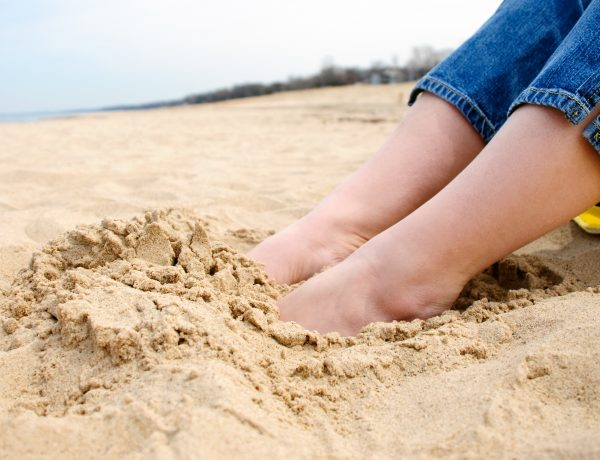 Picture of female feet buried in sand at the beach.
