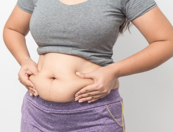 Overweight woman hand pinching excessive belly fat on gray background, Healthy concept